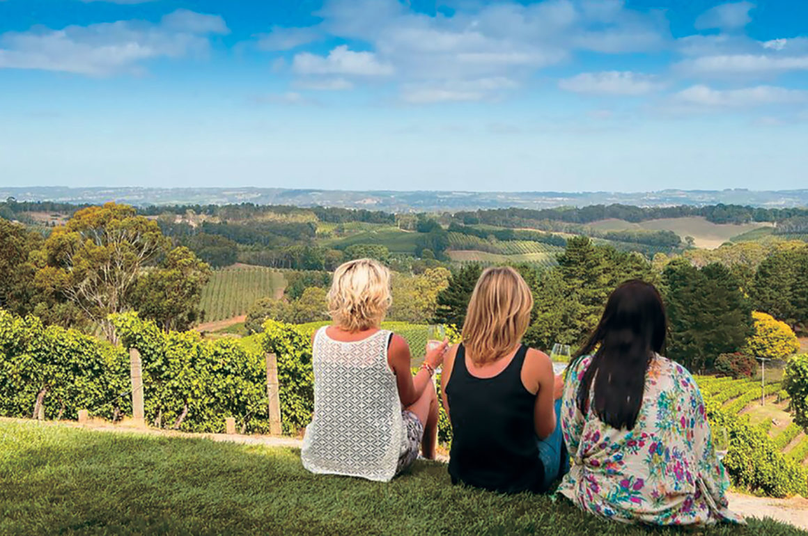 Three women sitting facing the vineyard