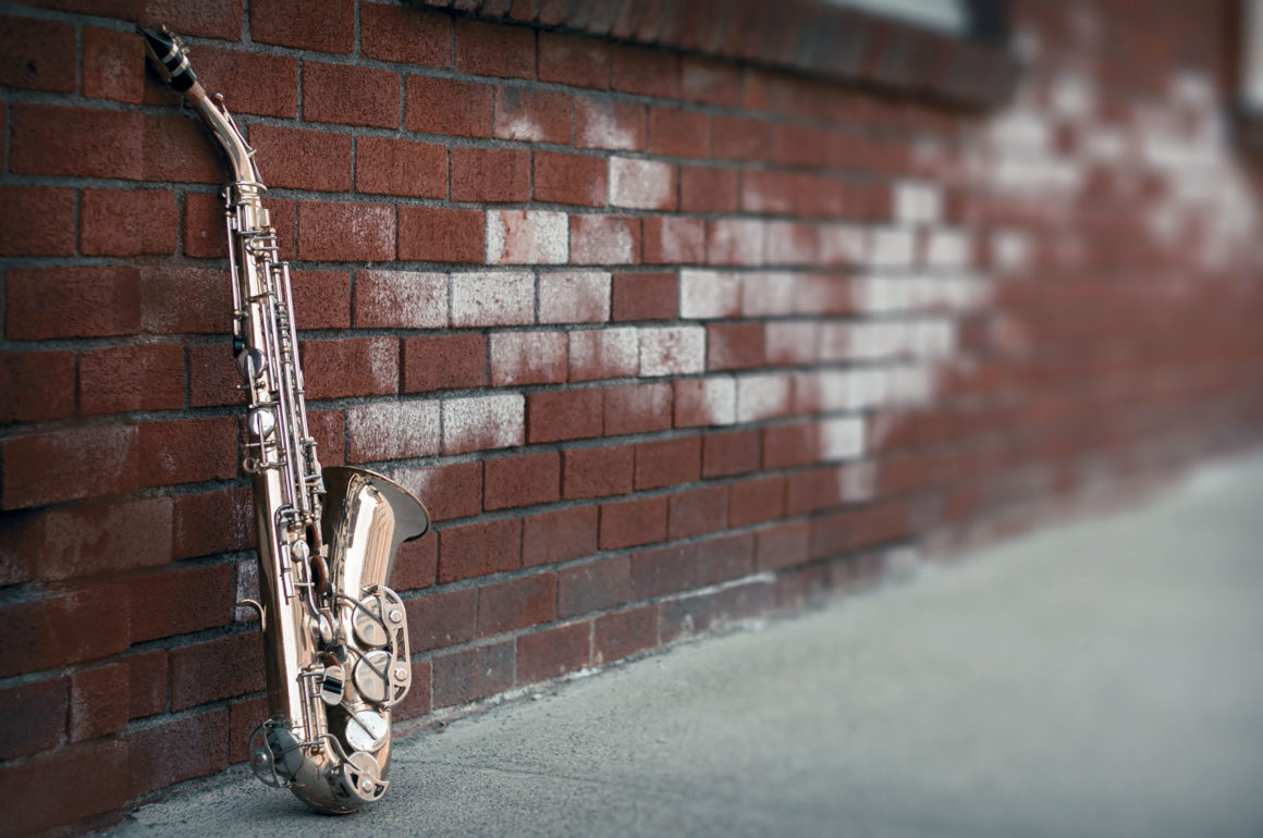 Saxophone leaning against a brick wall