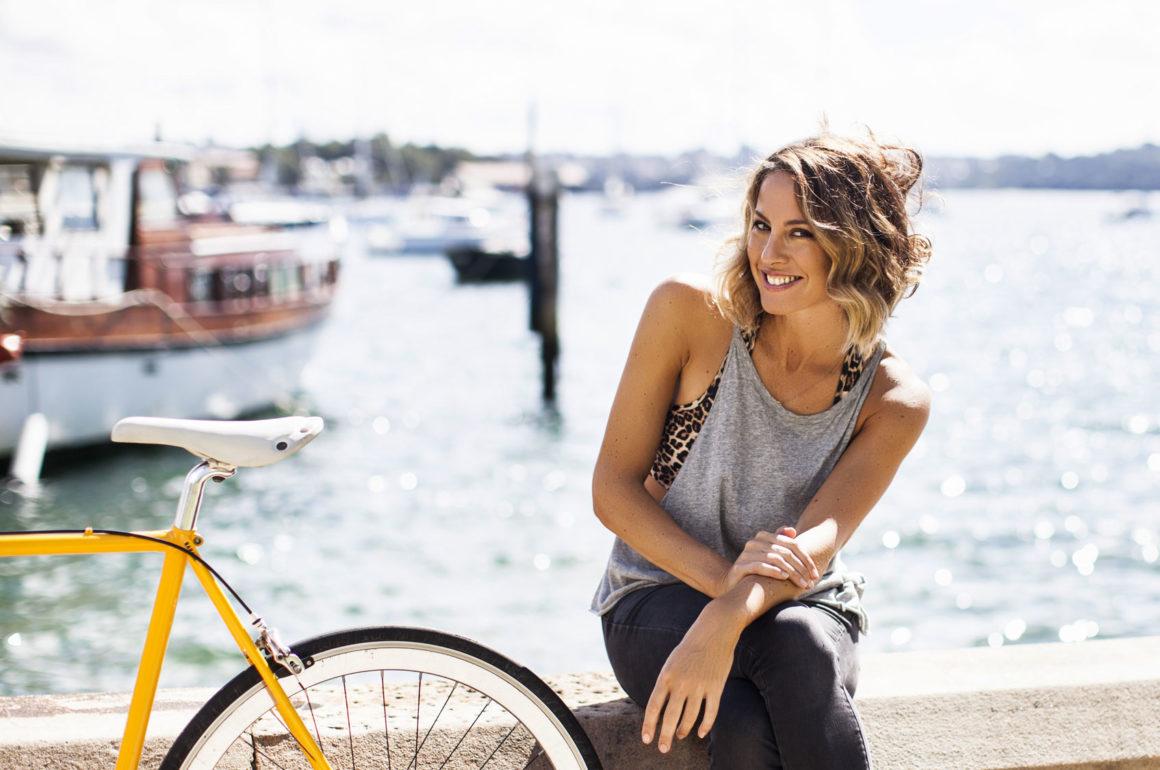 Sarah Wilson in sunshine beside the Sydney Harbour